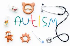 Childhood diseases. Word autism near stetoscope, pills, toys on white background top view.  Stock Photography