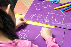 Childhood drawing. A young girl paints her masterpiece with bright colors Royalty Free Stock Image