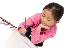 Childhood Drawing. A young asian girl drawing a picture. On white Stock Image
