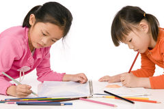 Childhood Drawing. A young asian girl drawing a picture. On white Royalty Free Stock Image