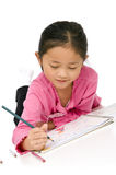 Childhood Drawing. A young asian girl drawing a picture. On white Royalty Free Stock Images