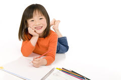 Childhood Drawing. A young asian girl drawing a picture. On white Stock Photo