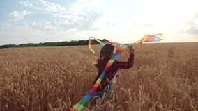 Childhood dream concept happy family. kid girl run with a kite in a field of wheat. daughter child play flying kite at