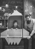 Childhood dreams. Boy play with dad, father, little cosmonaut sit in rocket made out of cardboard box. Child cute boy. Play cosmonaut, astronaut. Kid happy sit stock photo