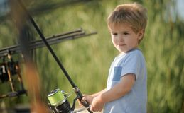 Childhood, education, training. Little boy learn to catch fish in lake or river. Fishing, angling, activity, adventure, sport. Summer vacation, hobby royalty free stock images