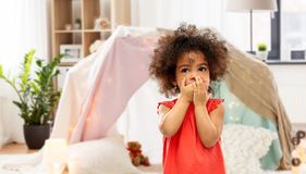 Confused african american girl covering mouth. Childhood, expressions and emotions concept - confused little african american girl covering mouth by hands over royalty free stock image