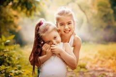 Childhood, family, friendship and people concept - two happy kids sisters hugging outdoors. Stock Photo
