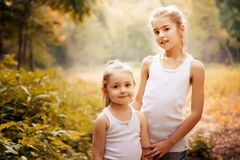 Childhood, family, friendship and people concept - two happy kids sisters hugging outdoors. Childhood, family, love, friendship and people concept - two happy Stock Photography