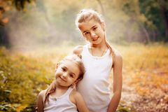 Childhood, family, friendship and people concept - two happy kids sisters hugging outdoors. stock photos