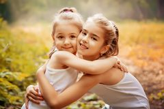 Childhood, family, friendship and people concept - two happy kids sisters hugging outdoors. Childhood, family, love, friendship and people concept - two happy Royalty Free Stock Photography