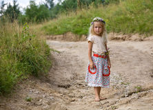 Childhood flowers. Little girl in wild flowers wreath standing barefoot on summer road royalty free stock photo