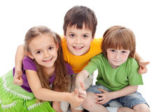 Childhood friends. Kids hugging and giving thumbs up sign Stock Images
