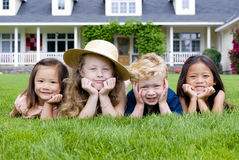 Childhood friends. A group of kids laying in the grass. Diveristy and friendship Royalty Free Stock Photos