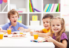 Childhood friends eating together. In kids room Royalty Free Stock Images