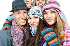 Childhood friends. Group of cheerful young people in warm clothes standing together. Friendship. Isolated over white Royalty Free Stock Image