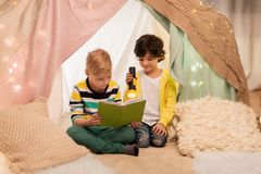 Happy boys reading book in kids tent at home. Childhood, friendship and hygge concept - happy little boys reading book with torch light in kids tent or teepee at Royalty Free Stock Image