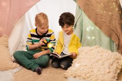 Happy boys reading book in kids tent at home. Childhood, friendship and hygge concept - happy little boys reading book with torch light in kids tent or teepee at Stock Photo