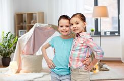 Happy smiling little girls hugging at home. Childhood, friendship and people concept - happy smiling little girls hugging at home over kids room and tepee Stock Photos