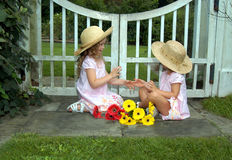 Childhood Games. Two sisters sit on sidewalk in a garden and play pat-a-cake.  Flowers sit at their feet.  Both are wearing straw hats and pink dresses.  A white Royalty Free Stock Photography
