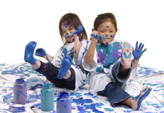 Childhood Girls floor painting. Two young girls having fun painting everything. Childhood, learning, exploration family Royalty Free Stock Images