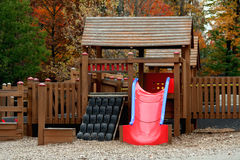 Childhood Guantlet. A childrens playground slide with tire climber Stock Photos