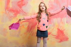 Childhood and happiness. Child girl with present pack on colorful background. Holiday celebration and party. Christmas and birthday. Small girl with shopping Royalty Free Stock Photography