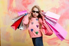 Childhood and happiness. Child girl with present pack on colorful background. Small girl with shopping bag. Holiday celebration and party. Christmas and Stock Images