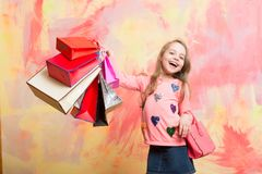 Childhood and happiness. Holiday celebration and party. Christmas and birthday. Child girl with present pack on colorful background. Small girl with shopping Royalty Free Stock Photos