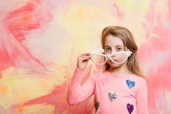 Childhood and happiness. Glasses on girl kid with serious face. Small girl in fashionable summer glasses. Child girl on colorful background. beauty and fashion Royalty Free Stock Photography
