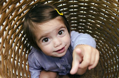 Childhood - Hide and Seek. Happy little girl playing peekaboo and hides inside a basket Stock Photo