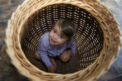 Childhood - Hide and Seek. Happy little girl playing peekaboo and hides inside a basket Royalty Free Stock Image
