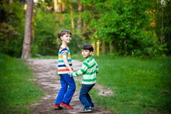 Childhood, hiking, family, friendship and people concept - two happy kids walking along forest path.  royalty free stock photo