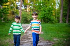 Childhood, hiking, family, friendship and people concept - two happy kids walking along forest path.  stock photography