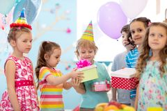 Childhood, holidays, celebration and friendship concept. Happy children in party hats giving gifts at birthday party stock images