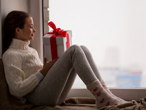 Girl with gift sitting on sill at home window Stock Photos