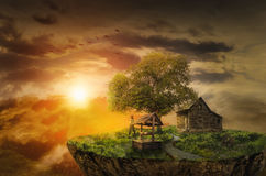 Childhood home. Lonely girl on the flying island looks at bright sunset next to the house of his childhood Stock Images