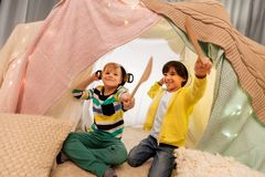 Boys with pots playing in kids tent at home. Childhood and hygge concept - happy little boys with cooking pots playing in kids tent at home stock photos