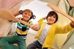 Boys with pots playing in kids tent at home. Childhood and hygge concept - happy little boys with cooking pots playing in kids tent at home royalty free stock images