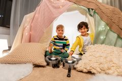 Boys with pots playing music in kids tent at home. Childhood and hygge concept - happy little boys with cooking pots playing music in kids tent at home stock images