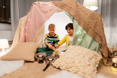 Boys with pots playing music in kids tent at home. Childhood and hygge concept - happy little boys with cooking pots playing music in kids tent at home royalty free stock image