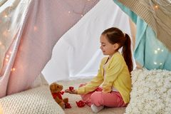 Girl playing tea party with teddy in kids tent. Childhood and hygge concept - happy little girl playing tea party with teddy bear in kids tent at home royalty free stock images