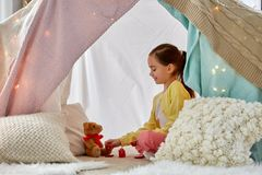 Girl playing tea party with teddy in kids tent. Childhood and hygge concept - happy little girl playing tea party with teddy bear in kids tent at home stock photography