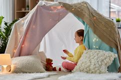 Girl playing tea party with teddy in kids tent. Childhood and hygge concept - happy little girl playing tea party with teddy bear in kids tent at home royalty free stock image