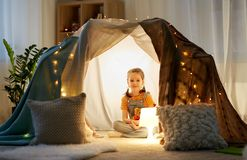 Little girl with toys in kids tent at home. Childhood and hygge concept - happy little girl with toys in kids tent at home stock images