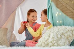 Little girl playing tea party in kids tent at home. Childhood and hygge concept - happy little girls playing tea party with toy crockery and clinking cups in royalty free stock photo