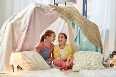 Little girl playing tea party in kids tent at home. Childhood and hygge concept - happy little girls playing tea party with toy crockery in kids tent at home stock photography