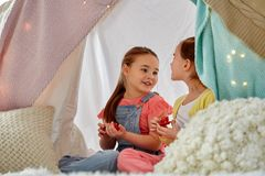 Little girl playing tea party in kids tent at home. Childhood and hygge concept - happy little girls playing tea party with toy crockery in kids tent at home stock photos