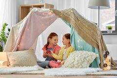 Little girl playing tea party in kids tent at home. Childhood and hygge concept - happy little girls playing tea party with toy crockery in kids tent at home stock image