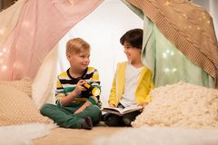 Happy boys reading book in kids tent at home. Childhood, hygge and friendship concept - happy boys reading book with torch light in kids tent or teepee at home Royalty Free Stock Photo
