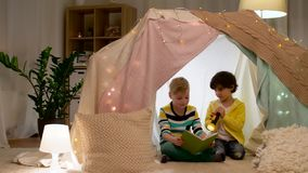 Happy boys reading book in kids tent at home stock footage